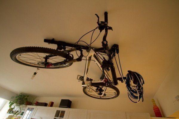 Велосипед притянут к потолку тросами, пропущенными через проушины, вкрученные в перекрытие
