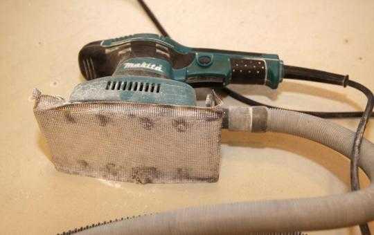 Вибрационная шлифмашинка с подключенным промышленным пылесосом.
