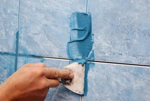 Затирка зазоров между плитками резиновым шпателем.